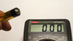 Measuring battery voltage using the digital multimeter Stock Footage