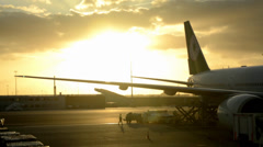 Wonderful sunset behind loading plane Stock Footage