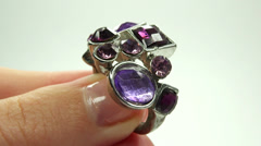 Jewelery ring with purple crystals putting on the finger Stock Footage