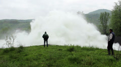 Two men stands and watches open dam discharged a large amount of water,tracking - stock footage