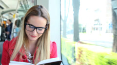 Stock Video Footage of Cute blond woman reading book while driving in tram
