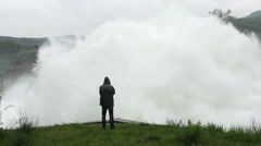 Man in raincoat stands and watches open dam discharged a large amount of water Stock Footage