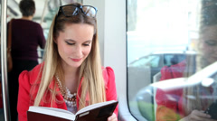 Blond young woman riding tram, reading book Stock Footage