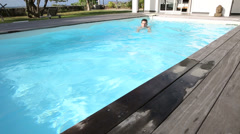 Man swimming in private swimming-pool Stock Footage