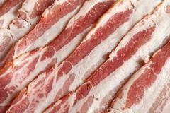 Slices of bacon fat over the entire surface - stock photo