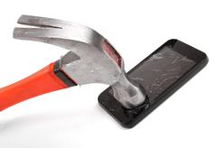 hammer and smartphone with smashed display - stock photo