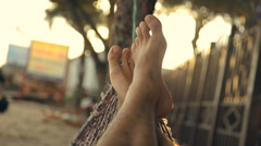Feet swinging in a hammock, POV. Relaxing on the beach at sunset. Stock Footage