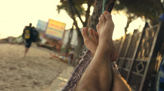 Feet swinging in a hammock, POV. Relaxing on the beach at sunset. - stock footage