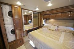 Recreation vehicle bedroom interior with washer and dryer in closet. luxury m Stock Photos