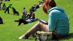 Woman reads kindle in the park Stock Footage