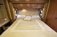 motorhome comfortable king size bed inside the slider. rv interior. - stock photo