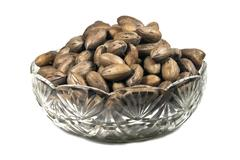 Decorative glass bowl filled with unshelled pecan nuts Stock Photos