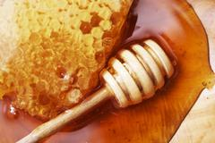 Honeycomb with wooden dipper on wooden plate closeup Stock Photos