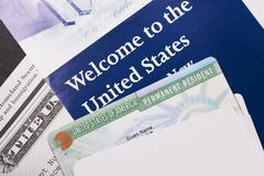 Stock Photo of welcome to the usa. immigration welcome letter and green card closeup. united