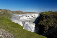 View of gulfoss (golden falls) waterfall and tourists wandering around, icela Stock Photos