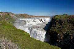 view of gulfoss (golden falls) waterfall and tourists wandering around, icela - stock photo