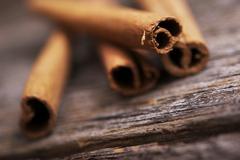 Fresh aromatic raw cinnamon sticks on aged wood. Stock Photos