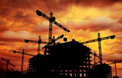 Construction sunset theme. construction cranes and building silhouette. Stock Illustration