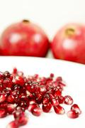 Pomegranate diet. fresh organic pomegranate seeds on white plate and whole fr Stock Photos