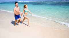 Couple running on sandy beach in caribbean island Stock Footage