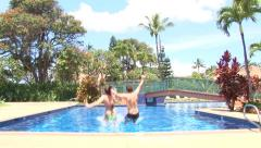 Happy Couple Jumping into Resort Pool Stock Footage