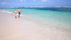 Cheerful couple running in crystal clear water Stock Footage