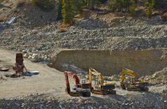 small gold mine operation. excavators and small sluice box. - stock photo