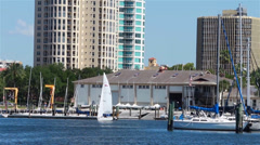Sailboat heading out against city backdrop - stock footage
