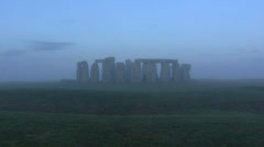 Stonehenge in mist, with the surrounding circular earth bank and ditch + zoom in Stock Footage