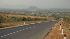 Road in the fields turns to the left. Town and mountains in the background. Stock Footage