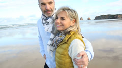 Cheerful senior couple walking on the beach Stock Footage