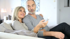 senior couple sitting in couch and watching tv - stock footage