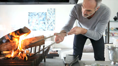 Mature man in modern house preparing fire Stock Footage