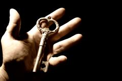 Human hand with an old key isolaten on black background Stock Photos