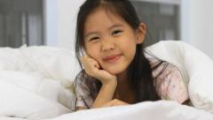 Little Asian girl play hide and seek on the bed Stock Footage