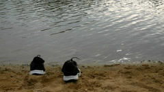 Black and white running shoes  on the orange sand of lake bank Stock Footage