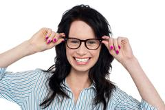 Joyous woman holding her spectacles - stock photo