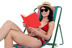 Enticing bikini model on a deckchair reading a book - stock photo
