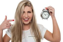 Girl pointing towards old fashioned time piece - stock photo