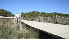 Couple walking on dunes wooden pontoon Stock Footage