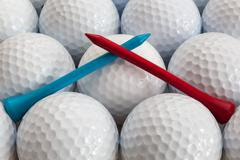An closeup of a regular a blue and red golf tees on a golf balls - stock photo