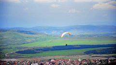 Following parachute abobe urban village Stock Footage
