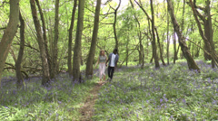 Attractive teenage couple walking in bluebell woods Stock Footage