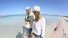 Couple walking on beautiful mediterranean beach Stock Footage