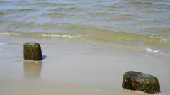 Stones at a beach with soft break-wave Stock Footage