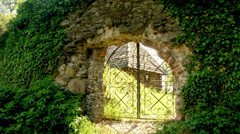 Ivy covered stone wall of the old castle, through the gate visible wooden house Stock Footage
