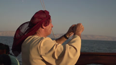 Man in Biblical Clothing on The Sea of Galilee Stock Footage