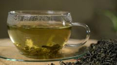 Loose tea and cup of tea, rotation of tea, studio lighting, panning Stock Footage