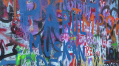 Person writing on Lennon Wall in Prague Stock Footage