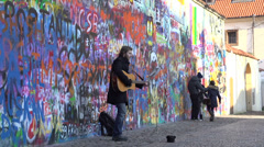 Man playing guitar in front of Lennon Wall Stock Footage